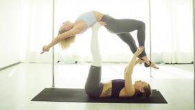 Twee jonge vrouwen die acrobatische yoga uitoefenen stock videobeelden