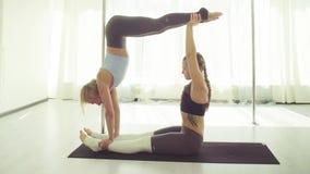 Twee jonge vrouwen die acrobatische yoga uitoefenen stock video