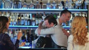 Twee jonge vrouwen die bij bar zitten, die met een barman spreken, de tweede barman komt Stock Fotografie