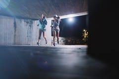 Twee jonge vrouwen die bij nacht in stad aanstoten stock afbeelding