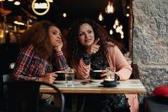 Twee jonge vrouwen die bij restaurant weg kijken Stock Foto