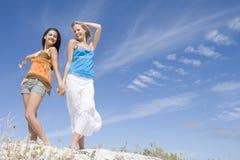 Twee jonge vrouwen die bij strand ontspannen royalty-vrije stock foto