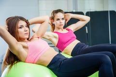 Twee jonge vrouwen die buikoefeningen doen die de gymnastiek- bal in een gymnastiek gebruiken stock foto