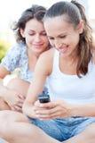 Twee jonge vrouwen die cellphone bekijken stock afbeeldingen