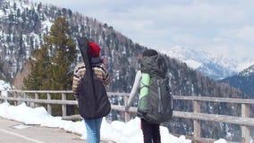 Twee jonge vrouwen die in Dolomiet met groot rugzakken en drinkwater reizen stock footage