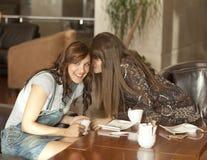 Twee jonge vrouwen die een geheim delen stock fotografie