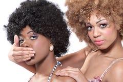 Twee jonge vrouwen die een geheim houden royalty-vrije stock afbeelding
