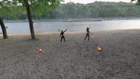 Twee jonge vrouwen die een show op het zand met vlam uitvoeren die zich op riverbank bevinden Bekwame fireshow vrouwelijke kunste stock footage