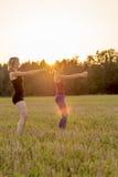 Twee jonge vrouwen die in een weide uitwerken Royalty-vrije Stock Foto's