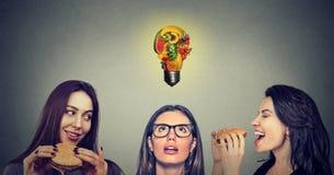Twee jonge vrouwen die hamburgers eten die beklemtoond nadenkend meisje met fruit bekijken vormden gloeilamp boven hoofd stock afbeeldingen