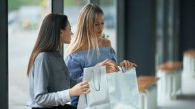 Twee jonge vrouwen die hun nieuwe aankopen met elkaar delen stock videobeelden