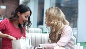 Twee jonge vrouwen die hun nieuwe aankopen met elkaar delen Stock Afbeeldingen