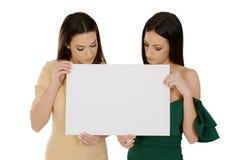 Twee jonge vrouwen die lege raad houden, die neer aan boord kijken stock fotografie