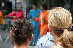 Twee jonge vrouwen die op de prestaties van de sambaband letten Stock Afbeeldingen