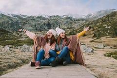 Twee jonge vrouwen die op de weide zitten die van aard geniet royalty-vrije stock afbeeldingen