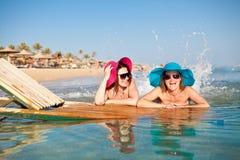 Twee jonge vrouwen die op het strand spuiten Royalty-vrije Stock Foto's
