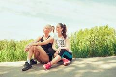 Twee jonge vrouwen die in openlucht in een park op zonnige de zomerdag zetten Royalty-vrije Stock Foto's