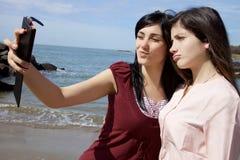 Twee jonge vrouwen die selfie voor strand nemen die grappige gezichten maken Royalty-vrije Stock Foto