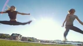 Twee jonge vrouwen die streng in sprongen uitvoeren in openlucht onder de zon stock video