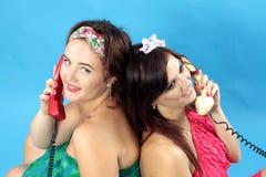 Twee jonge vrouwen die telefoons op blauwe achtergrond uitnodigen stock fotografie
