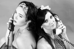 Twee jonge vrouwen die telefoons uitnodigen Royalty-vrije Stock Afbeeldingen