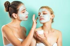 Twee jonge vrouwen die vochtinbrengende crèmeroom op hun gezicht toepassen Foto van zorgvuldige vrienden die kuuroordbehandelinge stock foto's