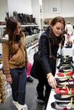Twee jonge vrouwen die voor schoenen winkelen Stock Foto