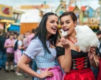 Twee jonge vrouwen in Dirndl kleden zich of tracht, lachend met gesponnen suikerzijde in Oktoberfest stock foto's