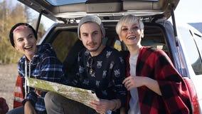 Twee jonge vrouwen en één man die kaart voor het zoeken van juiste weg gebruiken terwijl het zitten in de boomstam van de auto stock videobeelden
