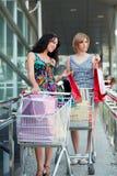 Twee jonge vrouwen met boodschappenwagentjes. Royalty-vrije Stock Foto's