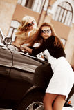 Twee jonge vrouwen met retro auto. stock foto's