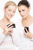 Twee jonge vrouwen met smartphones Stock Foto's