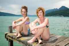 Twee jonge vrouwen natuurlijk te de waterkant Stock Foto's