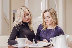 Twee jonge vrouwen op vergadering in conferentieruimte stock foto's