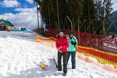 Twee jonge vrouwen in skikostuums die zich dichtbij de omheining in a bevinden ski-aangaande royalty-vrije stock afbeelding