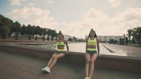 Twee jonge vrouwen in sporten die doend tricepsoefening met diaeffect kleden zich stock video