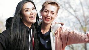 Twee jonge vrouwen verschillende nationaliteiten sluiten vrienden die een selfie nemen stock videobeelden