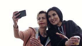 Twee jonge vrouwen verschillende nationaliteiten sluiten vrienden die een selfie nemen stock footage