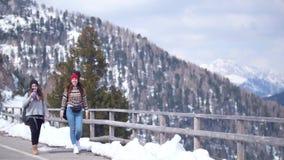Twee jonge vrouwentoerist die in Dolomiet met groot rugzak en gitaar drinkwater reizen stock video