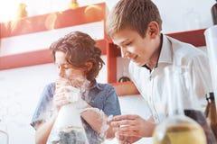 Twee jonge wetenschappers die chemisch experiment leiden op school stock afbeeldingen