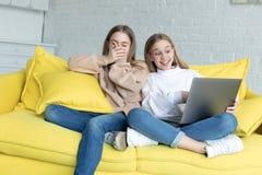 Twee jonge wijfjesvrienden die samen op grappige film op laptop letten terwijl thuis het zitten samen op bank stock foto