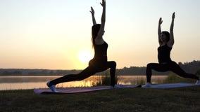 Twee jonge women do yoga vallen vooruit en strijdersoefeningen bij zonsondergang uit stock videobeelden