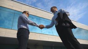 Twee jonge zakenlieden die dichtbij bureau samenkomen en elkaar begroeten Bedrijfsmens die een zwarte aktentas overgaan tot zijn  Stock Foto's