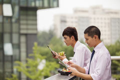 Twee jonge zakenlieden die en in openlucht over middagpauze werken eten Stock Fotografie