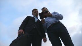 Twee jonge zakenlieden die en tabletpc spreken met behulp van openlucht Bedrijfsmensen die aan digitale tablet buiten met hemel w stock video