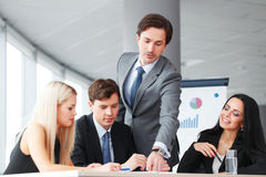 Twee jonge zakenlieden die over zaken spreken terwijl één van hen die op de computer leunen controleert Stock Afbeelding
