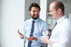 Twee jonge zakenlieden die over zaken spreken terwijl één van hen die op de computer leunen controleert Stock Afbeeldingen