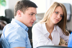 Twee jonge zakenlieden die over zaken spreken terwijl één van hen die op de computer leunen controleert Jonge succesvolle mens tw Stock Foto