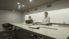 Twee jonge zakenliedenglimlachen aan camerazitting bij lijst op werkende plaats stock video