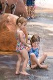 Twee jonge zusters die in water samen spelen stock foto